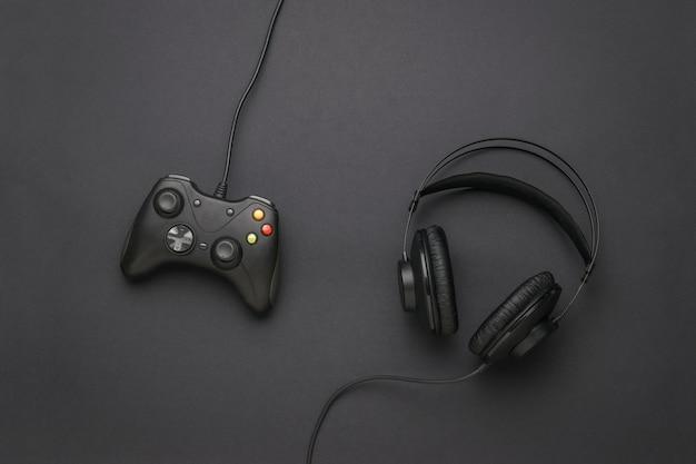 Bedrade koptelefoon en een bedrade gameconsole op een zwarte achtergrond. een apparaat voor het spelen van computerspelletjes. plat leggen. plaats voor tekst.