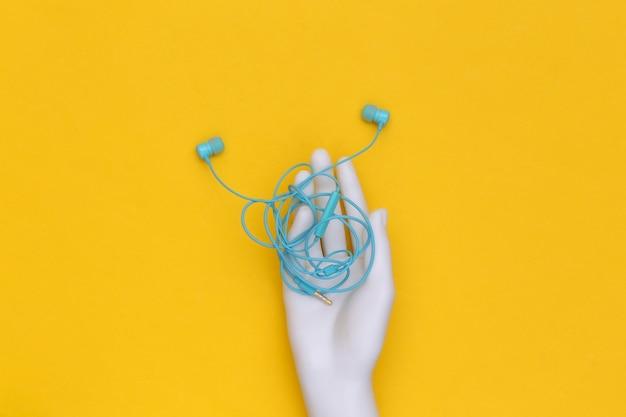 Bedrade verwarde koptelefoon in witte mannequin hand op gele achtergrond