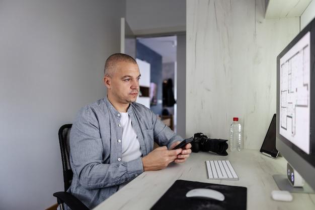 Bedrijf aan huis. een ontwerper, fotograaf of architect bevindt zich in een platte kamer voor een desktopcomputer. hij houdt de telefoon in zijn handen en bekeek de grafische tekening op het scherm freelance