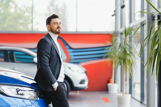 Bedrijf, autoverkoop, consumentisme en mensenconcept - gelukkige mens over autoshow of salonachtergrond