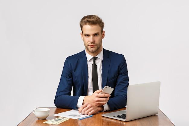 Bedrijf, bedrijf, bedrijfsconcept. ernstige baas zit in zijn kantoor met een gefocust, fronsend gezicht, houdt een smartphone vast, wacht een belangrijk gesprek, heeft veel geld op het spel