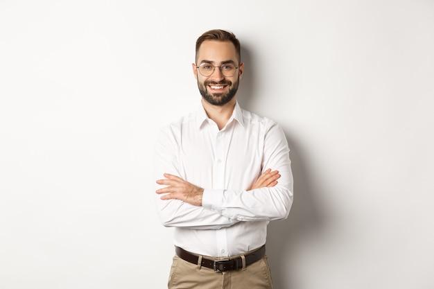 Bedrijf. jonge professionele zakenman die in glazen bij camera glimlachen, dwarsarm op borst