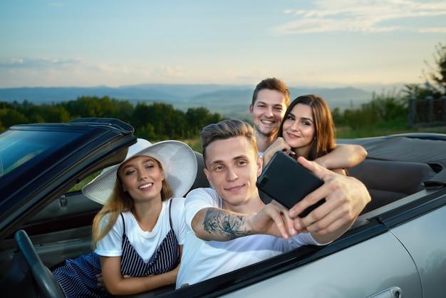 Bedrijf maakt selfie zittend in cabriolet.