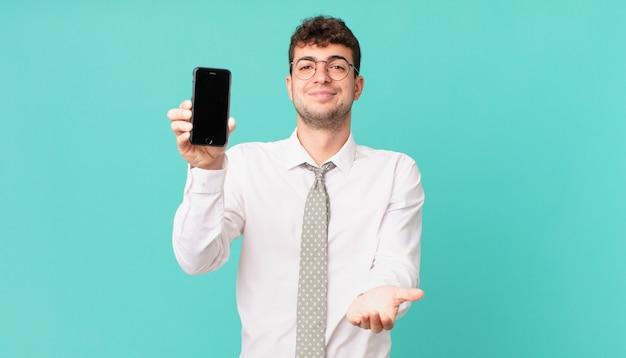 Bedrijf met een smartphone die vrolijk lacht met een vriendelijke, zelfverzekerde, positieve blik, een object of concept aanbiedt en toont