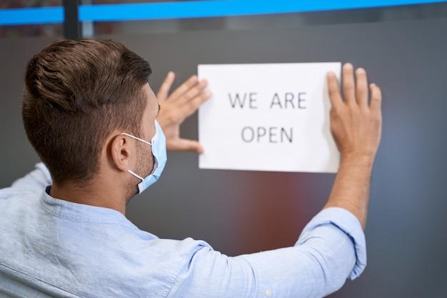 Bedrijf openen na afsluiting achteraanzicht van een jonge man met beschermend gezichtsmasker dat open teken steekt