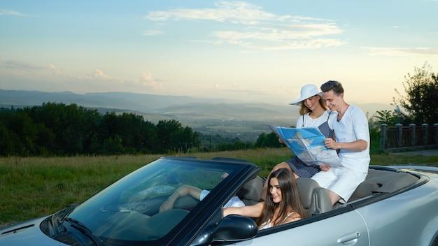 Bedrijf reist met de auto, koppel zit op cabriolet en houdt kaart.