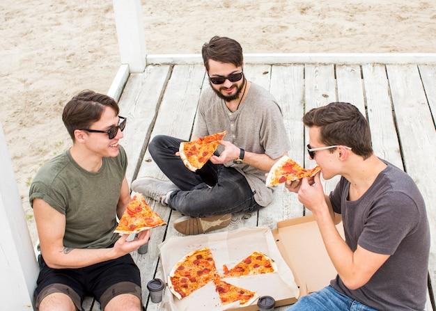 Bedrijf van jonge kerels die pizza op strand eten