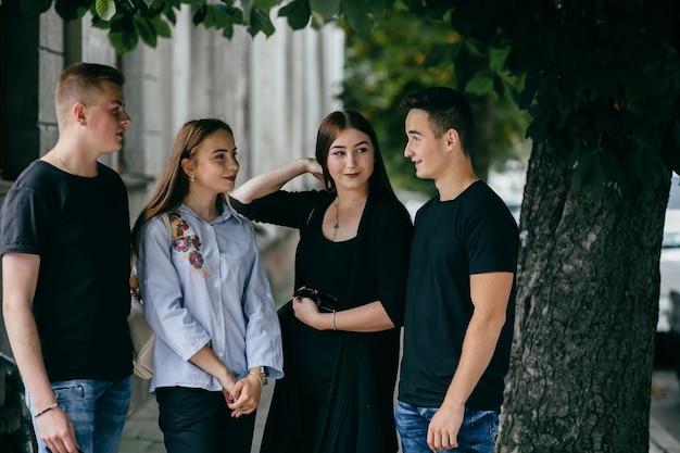 Bedrijf van jonge vrienden met smartphones die in de stad lopen