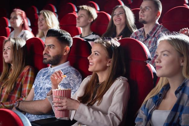 Bedrijf van lachende mooie vrouw kijken naar film.