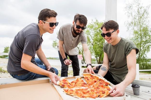 Bedrijf van lachende vrienden die pizza op picknick eten
