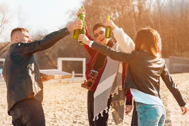Bedrijf van lachende vrienden met plezier met bier in de open lucht