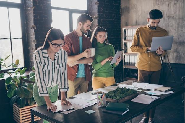 Bedrijf van vier mooie aantrekkelijke bekwame professionele gefocuste drukke serieuze mensen partners leiders opstellen verslag plan financiële strategie