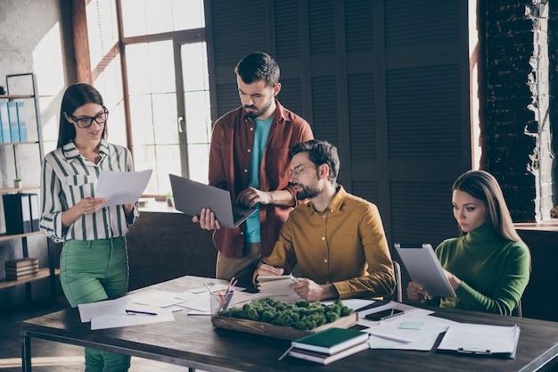 Bedrijf van vier mooie, aantrekkelijke professionele drukke mensen, makelaar, makelaar, maken van een onroerendgoedwebsite die een rapport opstellen en gegevens analyseren