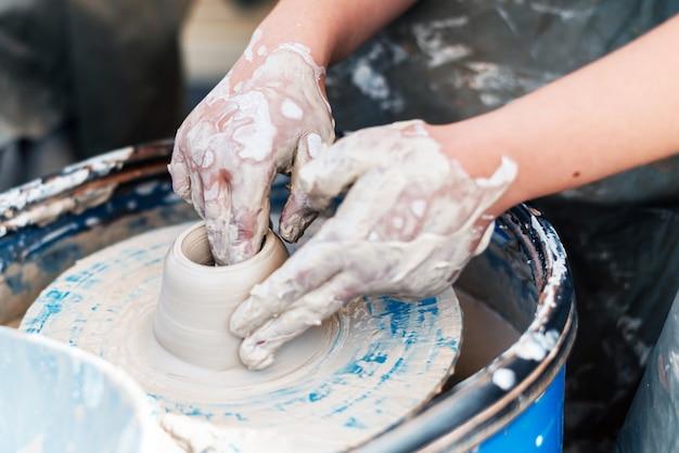 Bedrijf voor de productie van kleischotels in aardewerk met de handen van een persoon in het bedrijfsleven.