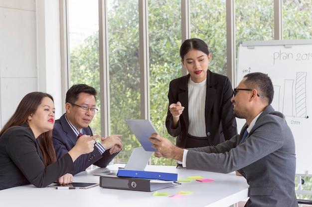 Bedrijf; zakelijke team en manager bespreken en delen ideeën in een vergadering.