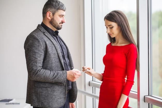 Bedrijf. zakenvrouw geeft geld aan mannen. vrouw gekleed in rode jurk geeft steekpenningen. zakenman in grijze jas krijgt omkoping. hoge resolutie
