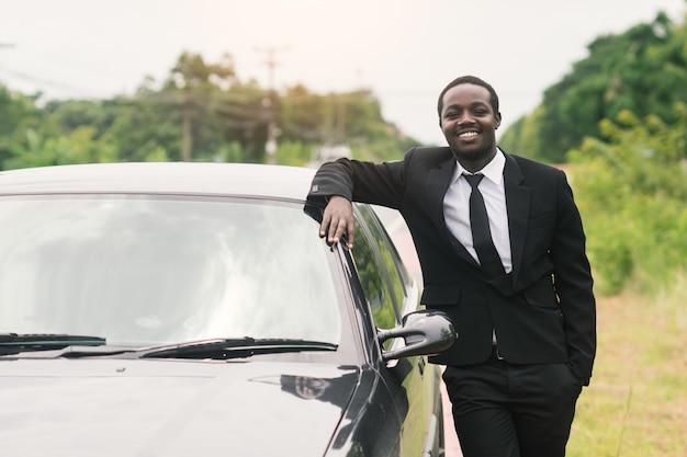 Bedrijfs afrikaanse mens die zich voor zijn auto bevindt.