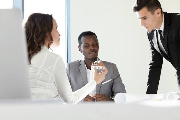 Bedrijfs-, architectuur- en kantoorconcept. groep architecten en ontwerpers die in bureau samenwerken, architecturaal project bespreken.
