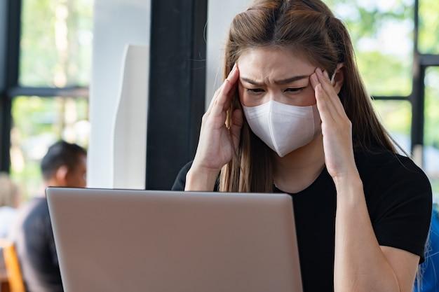 Bedrijfs aziatische jonge vrouw die met computerlaptop werken en beschermingsmasker dragen