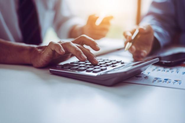 Bedrijfs aziatische middenleeftijdsmensen die calculator gebruiken om financiënrekeningen te berekenen.