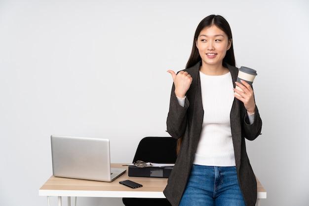 Bedrijfs aziatische vrouw die in haar werkplaats op witte muur aan de kant richten om een product voor te stellen