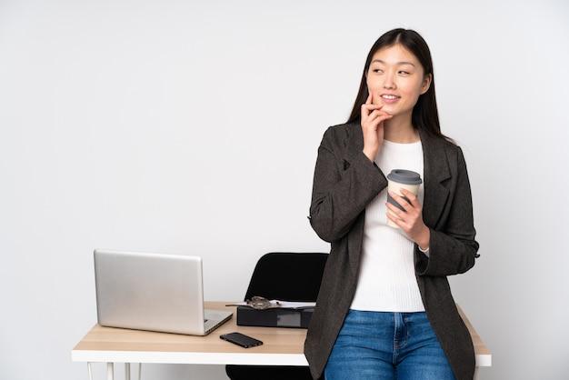 Bedrijfs aziatische vrouw die in haar werkplaats op witte muur een idee denken terwijl omhoog het kijken