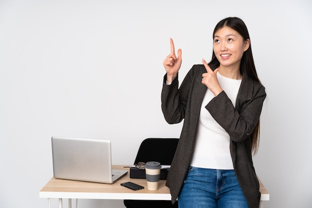 Bedrijfs aziatische vrouw die in haar werkplaats op witte muur met de wijsvinger een groot idee richten
