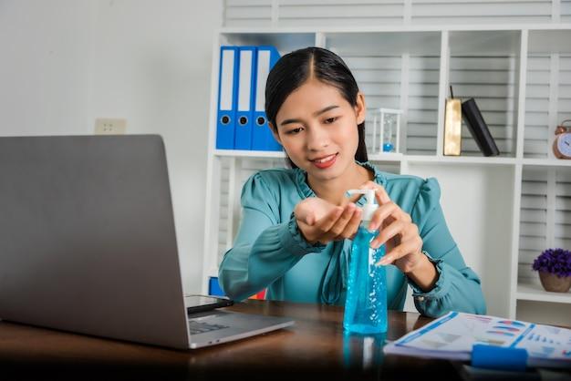 Bedrijfs aziatische vrouw die van huis werken en haar handen met ontsmettingsmiddelgel schoonmaken.
