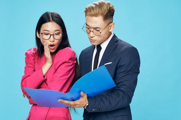 Bedrijfs aziatische vrouw en man die bedrijfsdocumenten kijken