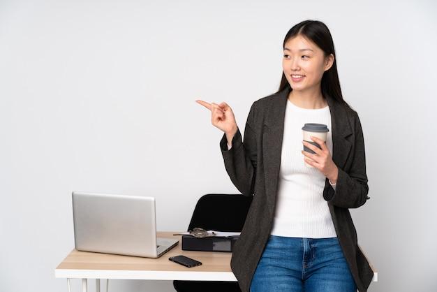 Bedrijfs aziatische vrouw in haar werkplaats op witte muur die vinger aan de kant richten