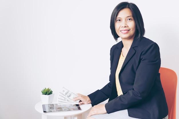 Bedrijfs aziatische vrouwenbeambte holding tablet smiling en gelukkig