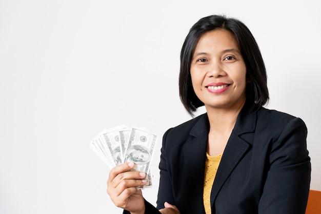 Bedrijfs aziatische vrouwenkantoormanager holding banknote op wit, glimlachend en gelukkig