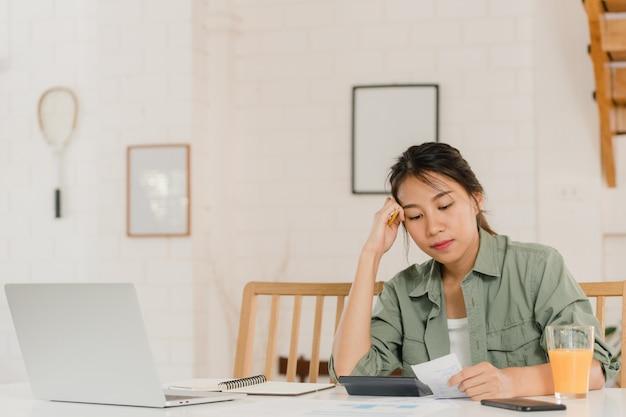 Bedrijfs aziatische vrouwenverslagen van inkomsten en uitgaven thuis