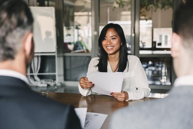 Bedrijfs-, carrière- en plaatsingsconcept - jonge aziatische vrouw die glimlacht en cv vasthoudt, zittend voor bestuurders tijdens zakelijke bijeenkomst of sollicitatiegesprek