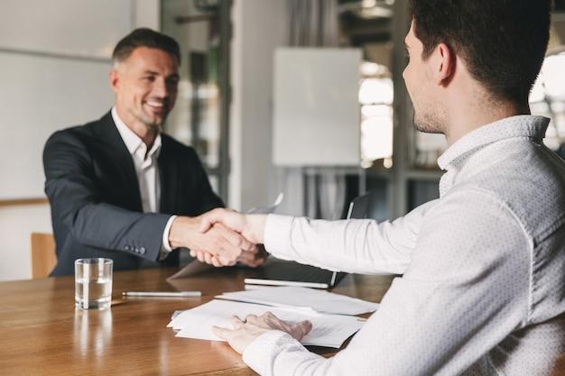 Bedrijfs-, carrière- en plaatsingsconcept - succesvolle jonge man die lacht en handdruk met europese zakenman na succesvolle onderhandelingen of interview op kantoor