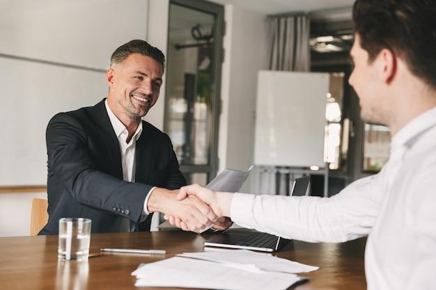 Bedrijfs-, carrière- en plaatsingsconcept - vrolijke knappe zakenman 30s glimlachend en handen schudden met mannelijke kandidaat, die werd gerekruteerd tijdens interview op kantoor