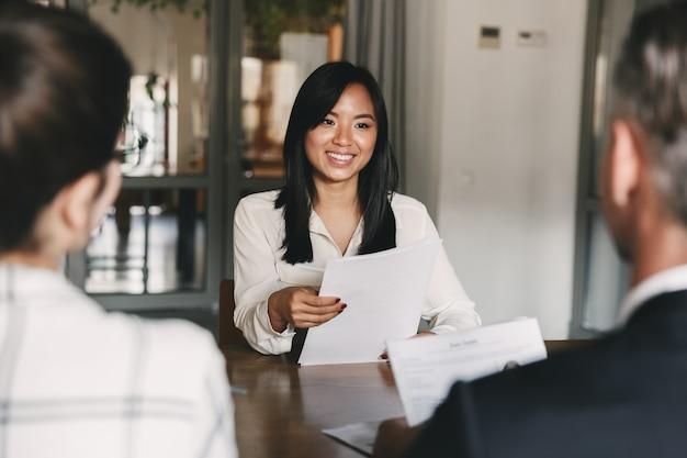 Bedrijfs-, carrière- en rekruteringsconcept - jonge aziatische vrouw die glimlacht en cv vasthoudt, tijdens het interviewen als kandidaat voor een baan in een groot bedrijf