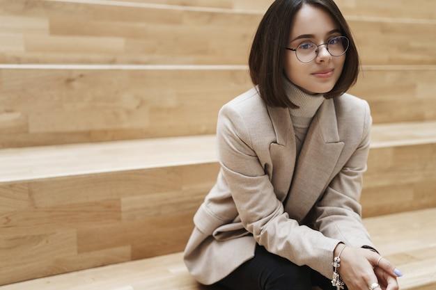 Bedrijfs-, carrière- en vrouwenconcept. portret van vrolijke succesvolle jonge vrouw in beige jas, zittend in collegezaal, kantoor lounge, glimlachend en op zoek blije camera.
