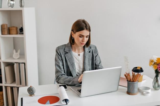 Bedrijfs dame in grijs jasje dat in laptop werkt. portret van een vrouw in kantoor.