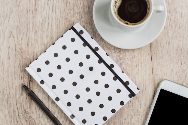 Bedrijfs en bureauconcept - het zwart-witte notitieboekje, de smartphone en de kop van de stipdekking op zwarte koffie op houten lijst. bovenaanzicht.