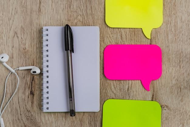 Bedrijfs en bureauconcept - leeg notitieboekje, hoofdtelefoons, stickers en zwarte pen op houten lijst. minimaal plat liggend, bovenaanzicht.