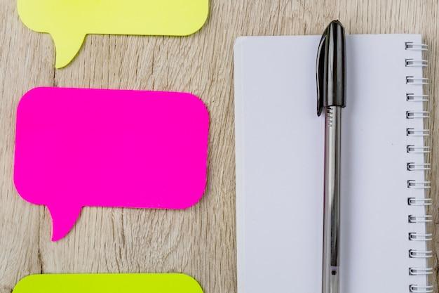 Bedrijfs en bureauconcept - leeg notitieboekje, stickers en zwarte pen op houten lijst. minimaal plat liggend, bovenaanzicht.