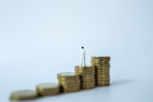 Bedrijfs- en gezondheidszorgconcept. miniatuur het cijfermensen van de arts die zich bovenop stapel muntstukken op witte achtergrond bevinden.