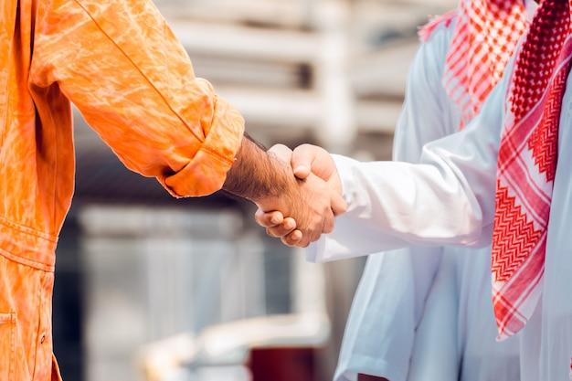 Bedrijfs- en kantoorconcept - arabische en zakenman schudden hand op stadsgezicht achtergrond