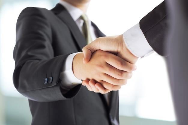 Bedrijfs- en kantoorconcept - zakenman handen schudden Premium Foto