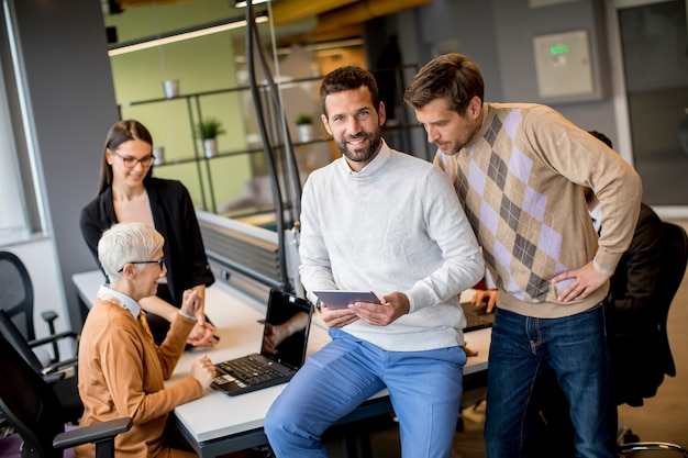 Bedrijfs en mensen die terwijl status in het bureau samen met collega's werken die op de achtergrond zitten communiceren