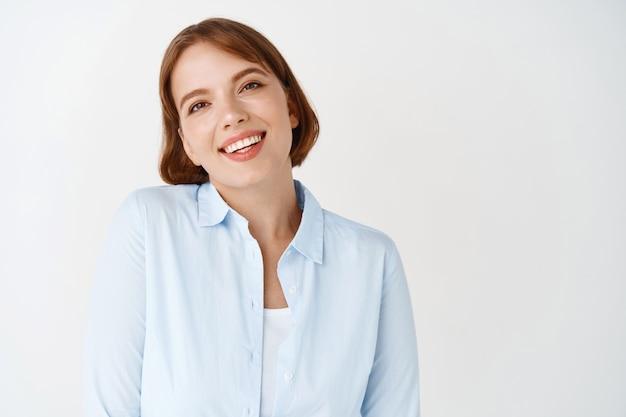 Bedrijfs- en mensenconcept. portret van een glimlachende jonge vrouw in blouse die er gelukkig uitziet, staande op een witte muur