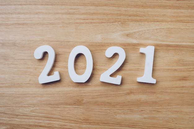 Bedrijfs- en ontwerpconcept - houten nummer 2021 voor gelukkig nieuwjaar tekst op houten tafel.