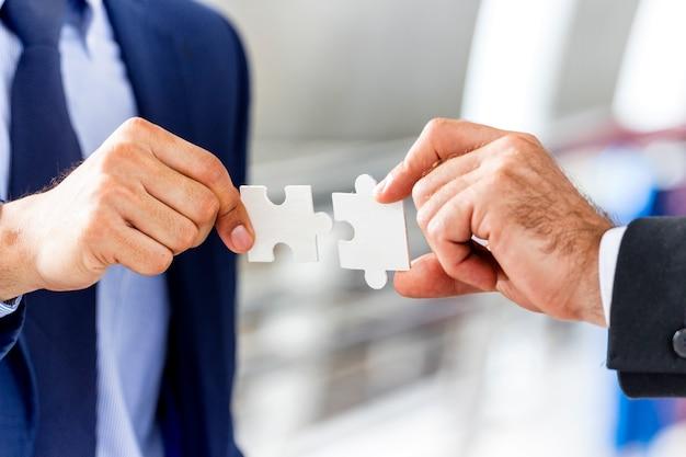 Bedrijfs- en teamwork-concept; zakelijke handen zetten puzzel stuk samen.