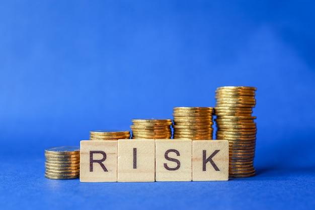 Bedrijfs-, geld- en risicobeheerconcept. close-up van engels brieven houten blok met stapel muntstukken op blauwe achtergrond.